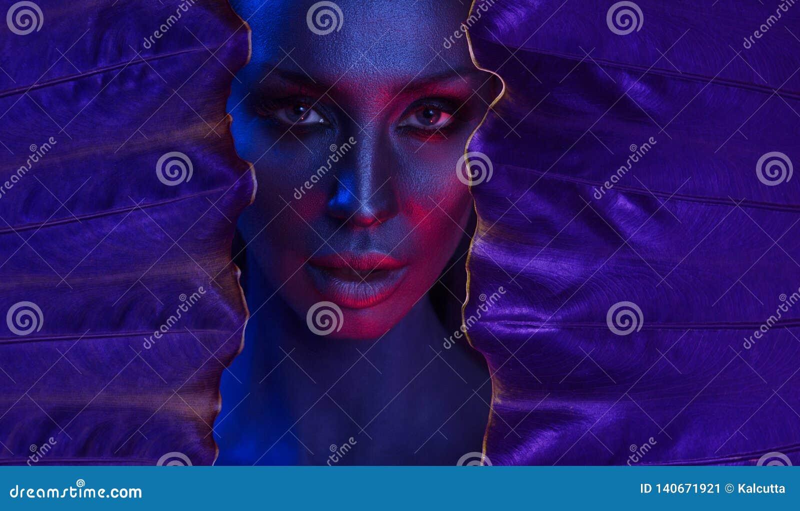 Retrato de neón del arte de la mujer joven hermosa con maquillaje místico atractivo