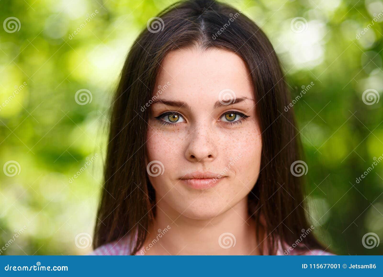 Retrato de olhos verdes freckled bonito novo da cara da mulher com hea