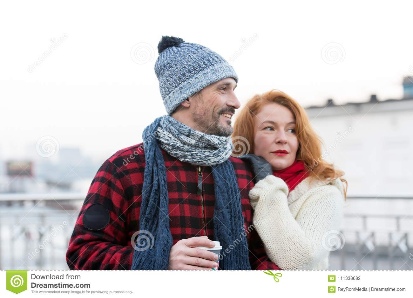 Retrato de pares felizes com copo de café O par tem a data na rua da cidade Pares loving que olham à maneira direita