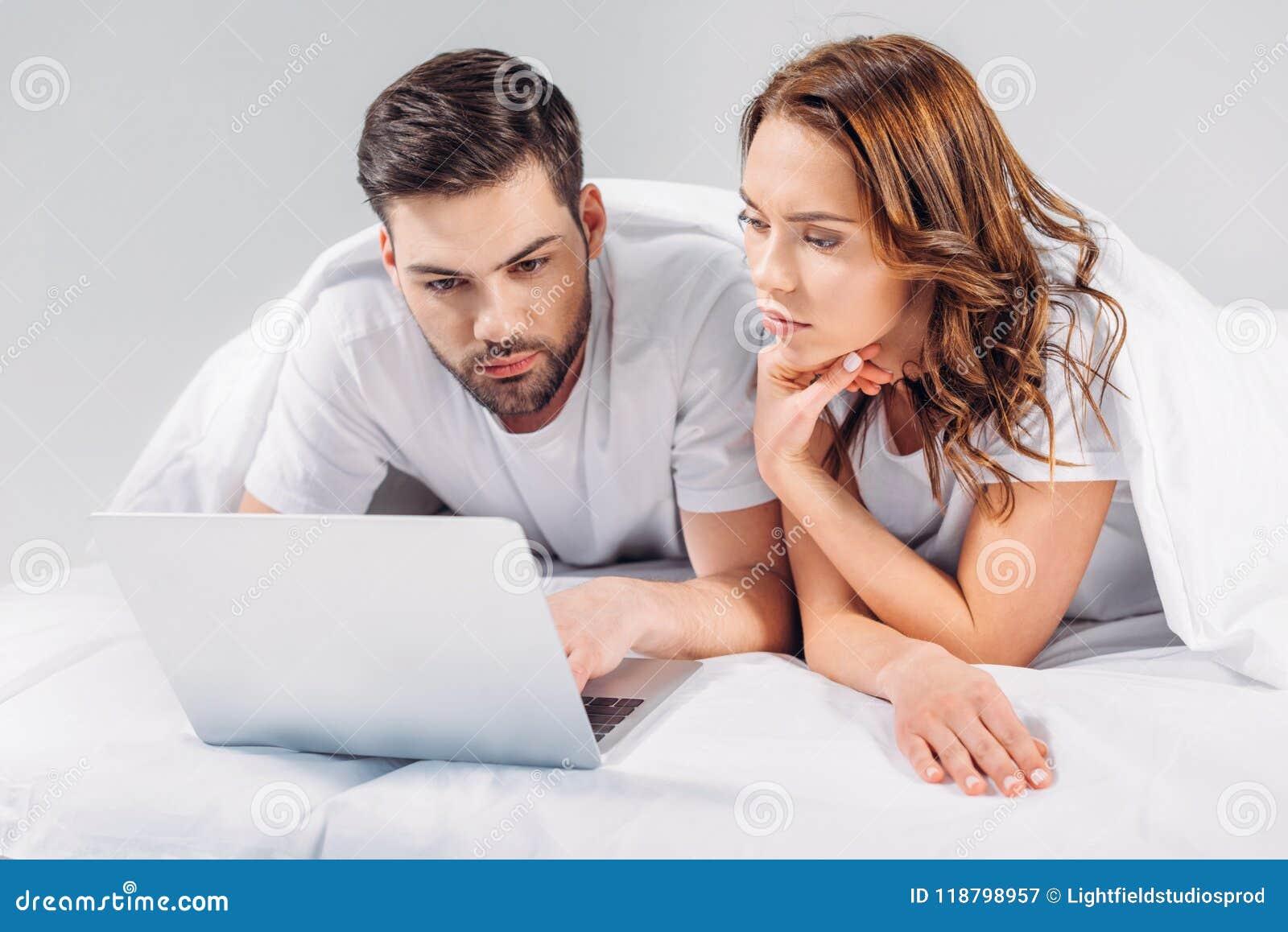 Retrato de pares focalizados usando o portátil ao descansar na cama junto