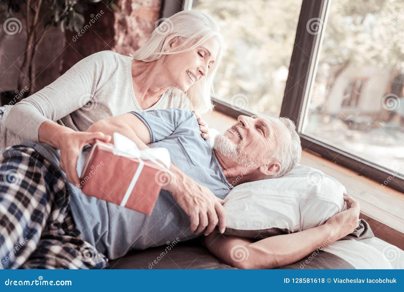 Retrato de pares idosos positivos com um presente