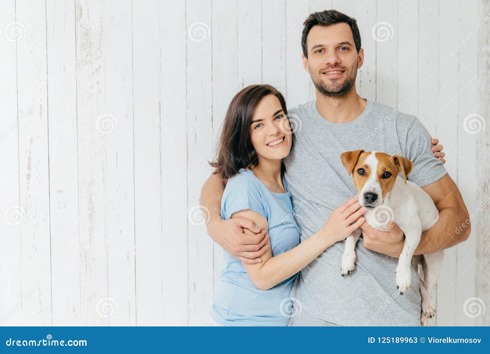 Retrato de pares novos da família para abraçar-se e guardar o thei