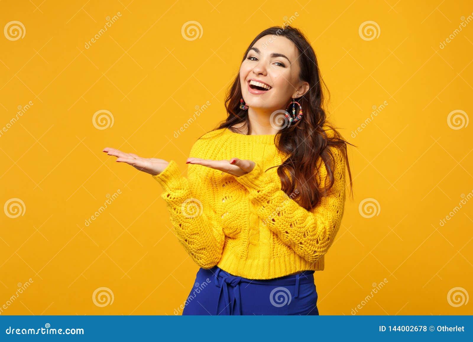 Retrato de reír a la mujer joven en el suéter, pantalones azules que miran la cámara señalando las manos a un lado aisladas en am