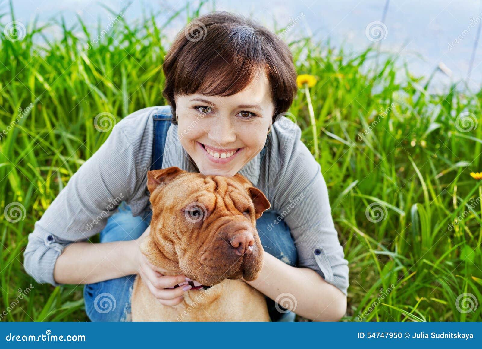 Retrato de rir a jovem mulher feliz nos macacões da sarja de Nimes que abraçam seu cão bonito vermelho Shar Pei na grama verde no