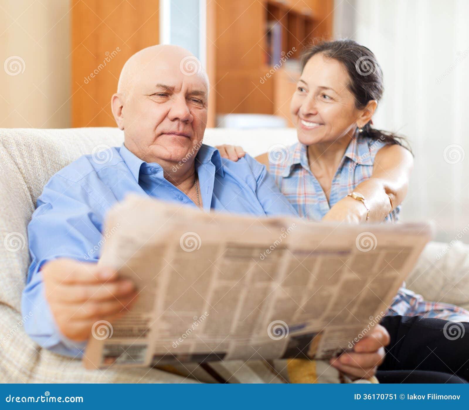 Retrato de rir a mulher madura e o homem idoso com jornal