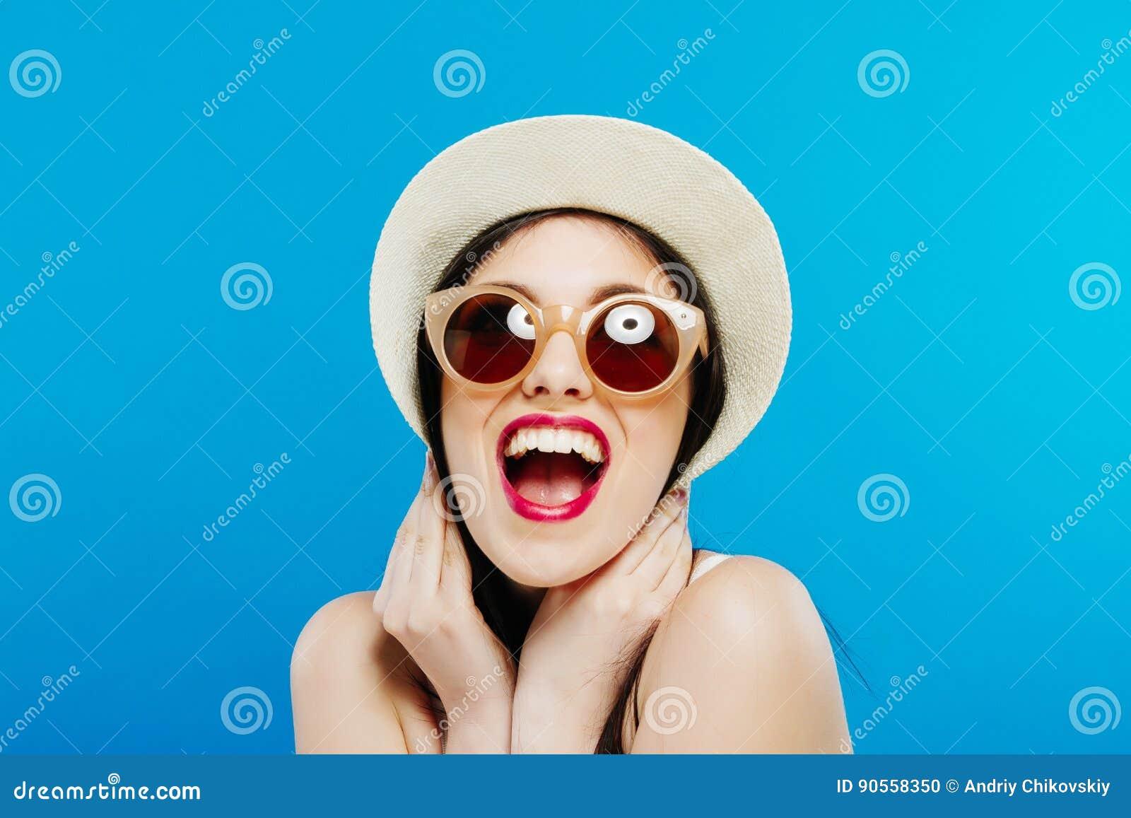Retrato de rir o modelo fêmea em óculos de sol da forma e em chapéu do verão no fundo azul