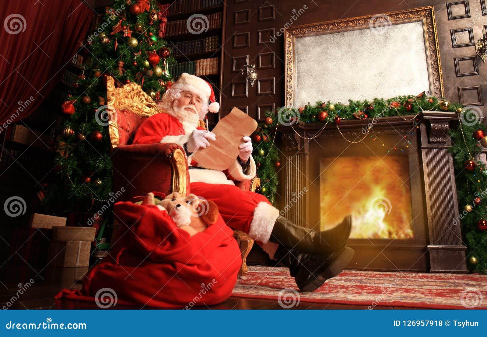 Retrato de Santa Claus feliz que senta-se em sua sala em casa perto da árvore de Natal e que lê a letra ou a lista de objetivos p