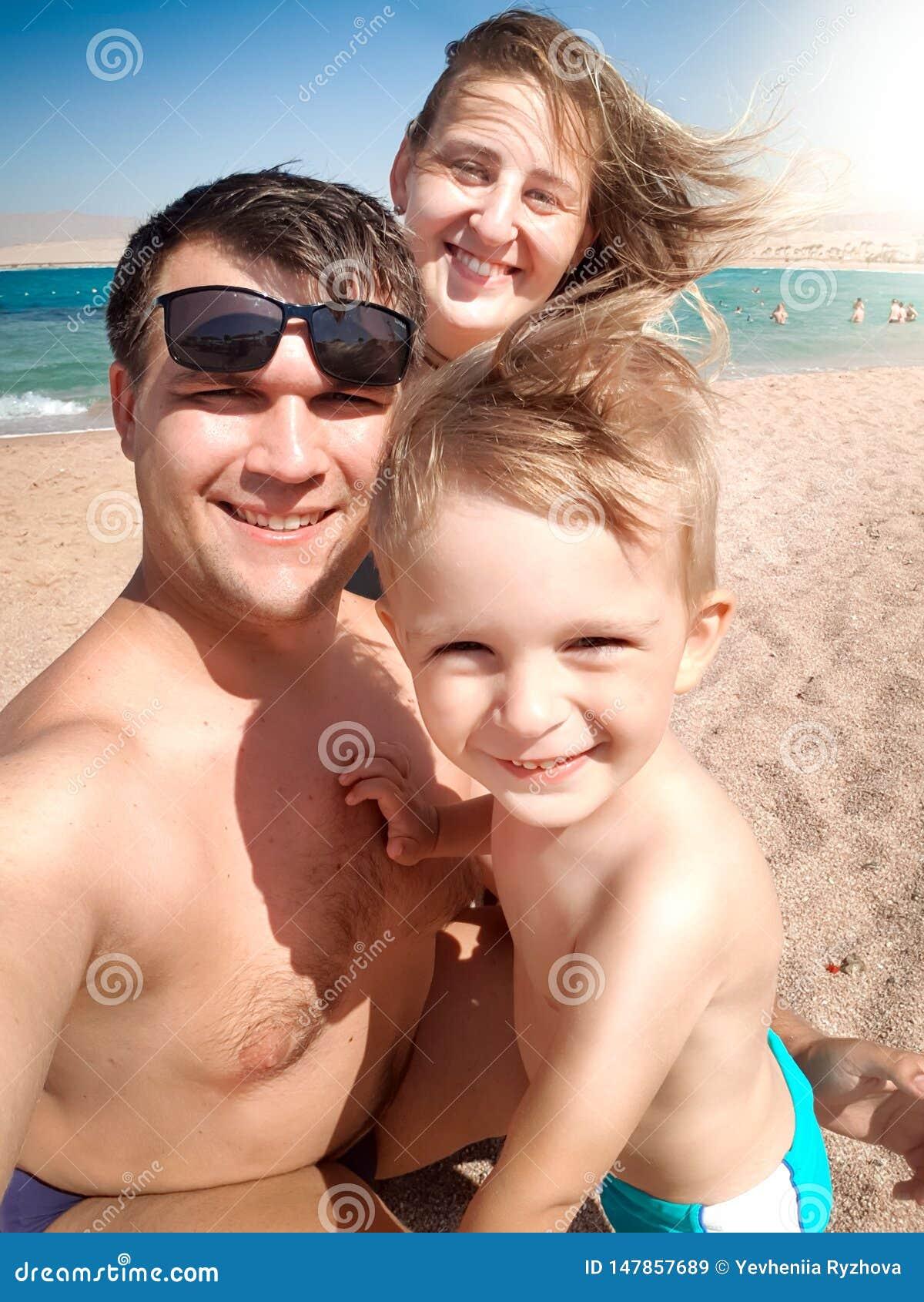 Retrato de Selfie de la familia alegre sonriente feliz en la playa del mar en el día ventoso soleado Familia que relaja y que tie
