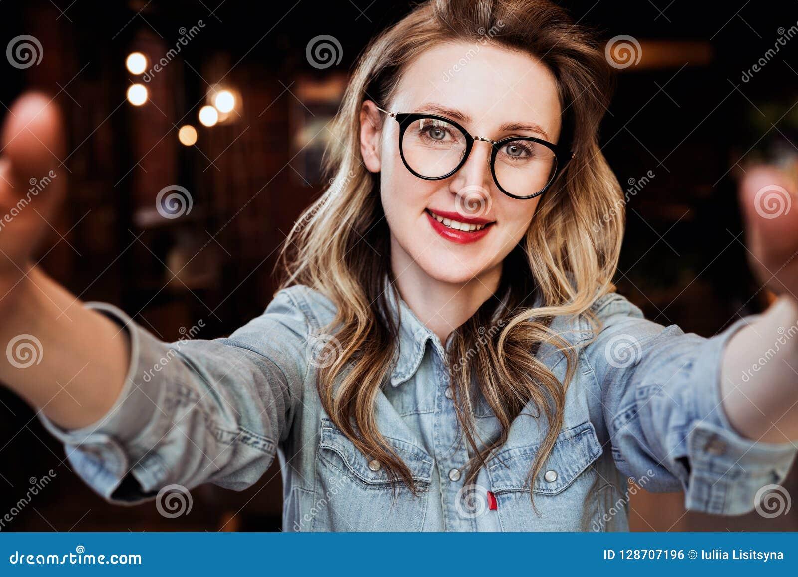 Retrato de Selfie de la mujer sonriente joven que se sienta en café La muchacha del inconformista en vidrios de moda toma un self