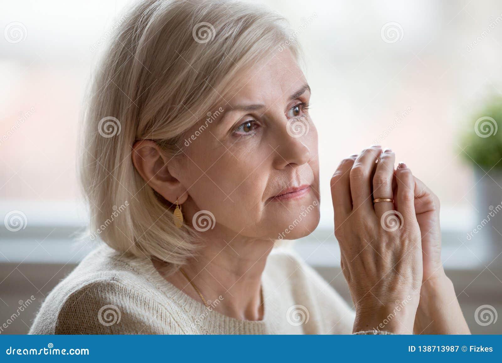 Retrato de sentarse cogitating de la mujer triste en casa solamente