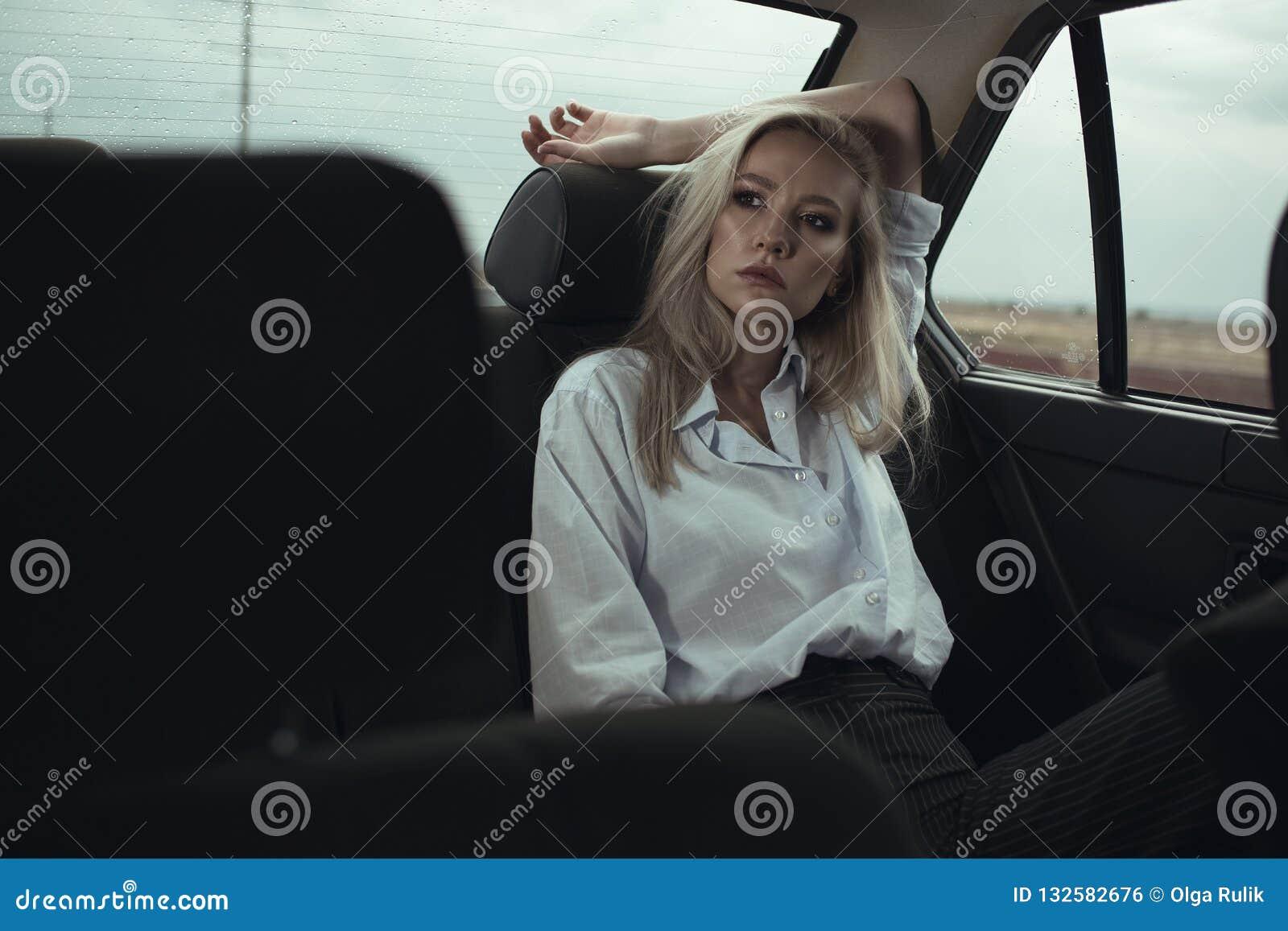 Retrato de sentarse hermoso de la mujer relajado en el asiento trasero del coche y de mirar la ventana cuidadosamente