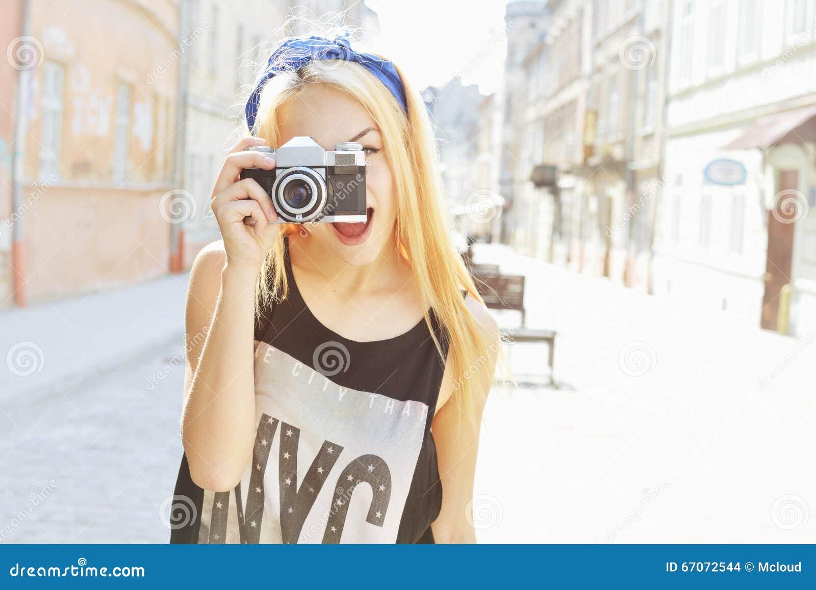 Retrato de sorriso do estilo de vida do verão exterior da jovem mulher bonita que tem o divertimento na cidade em Europa com câme