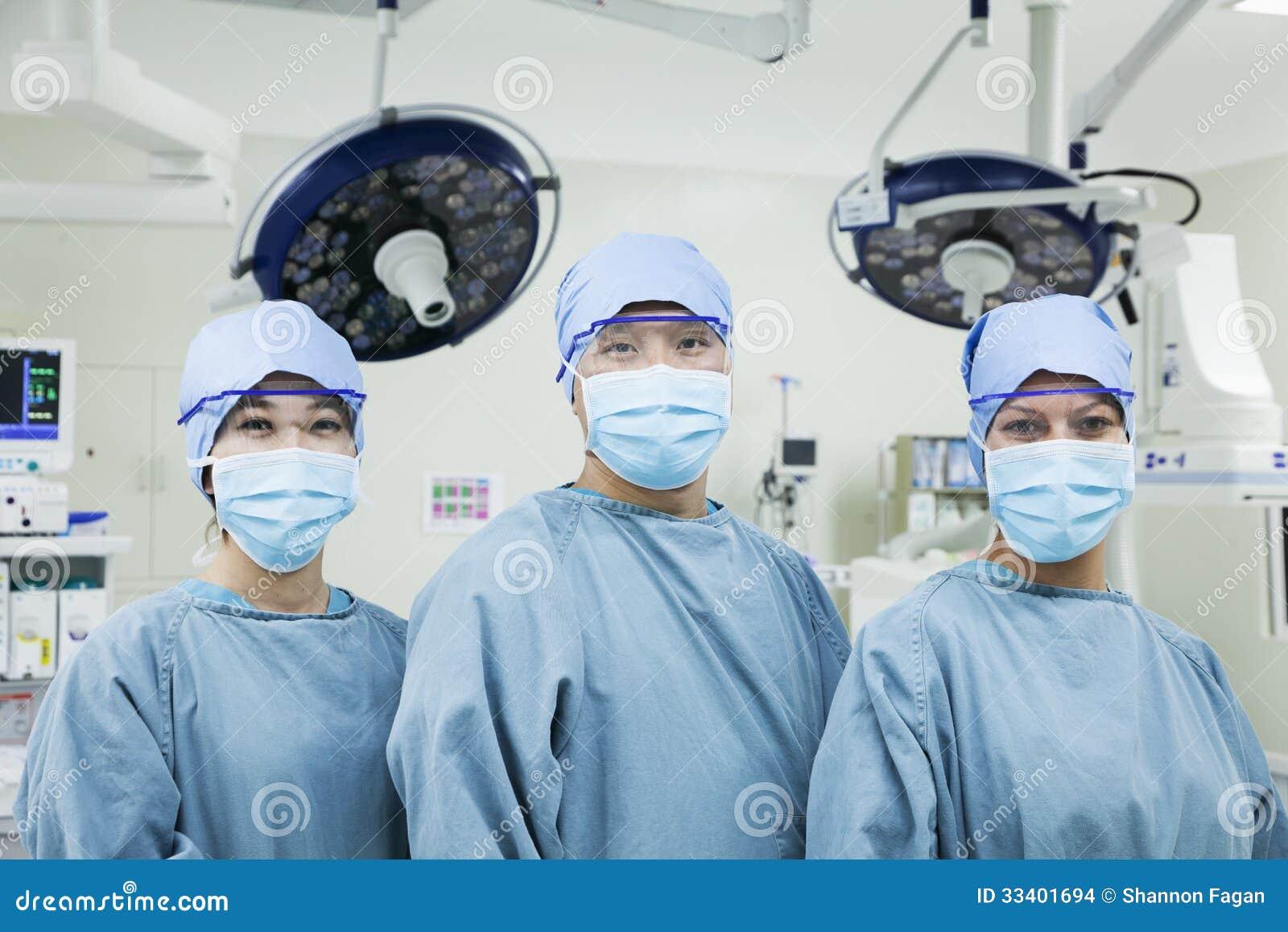 Retrato de três cirurgiões em seguido que vestem máscaras cirúrgicas na sala de operações, olhando a câmera