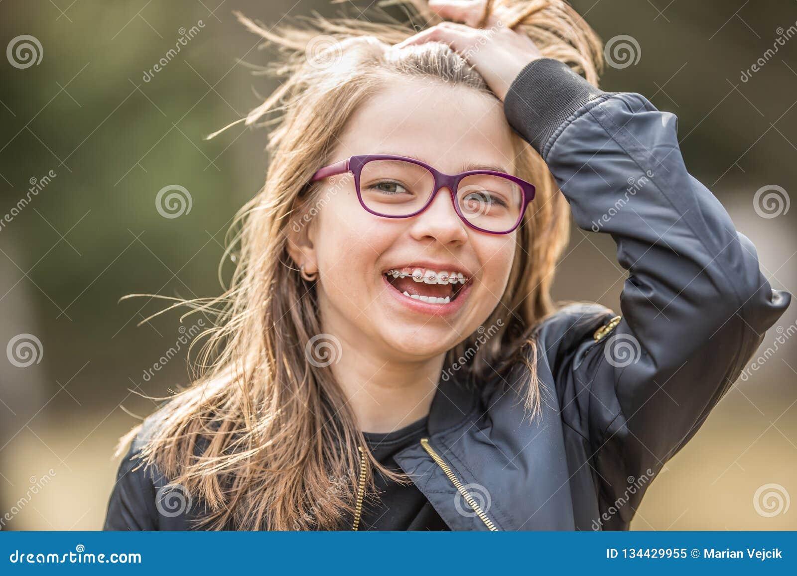 Retrato de um adolescente de sorriso feliz com cintas e vidros dentais