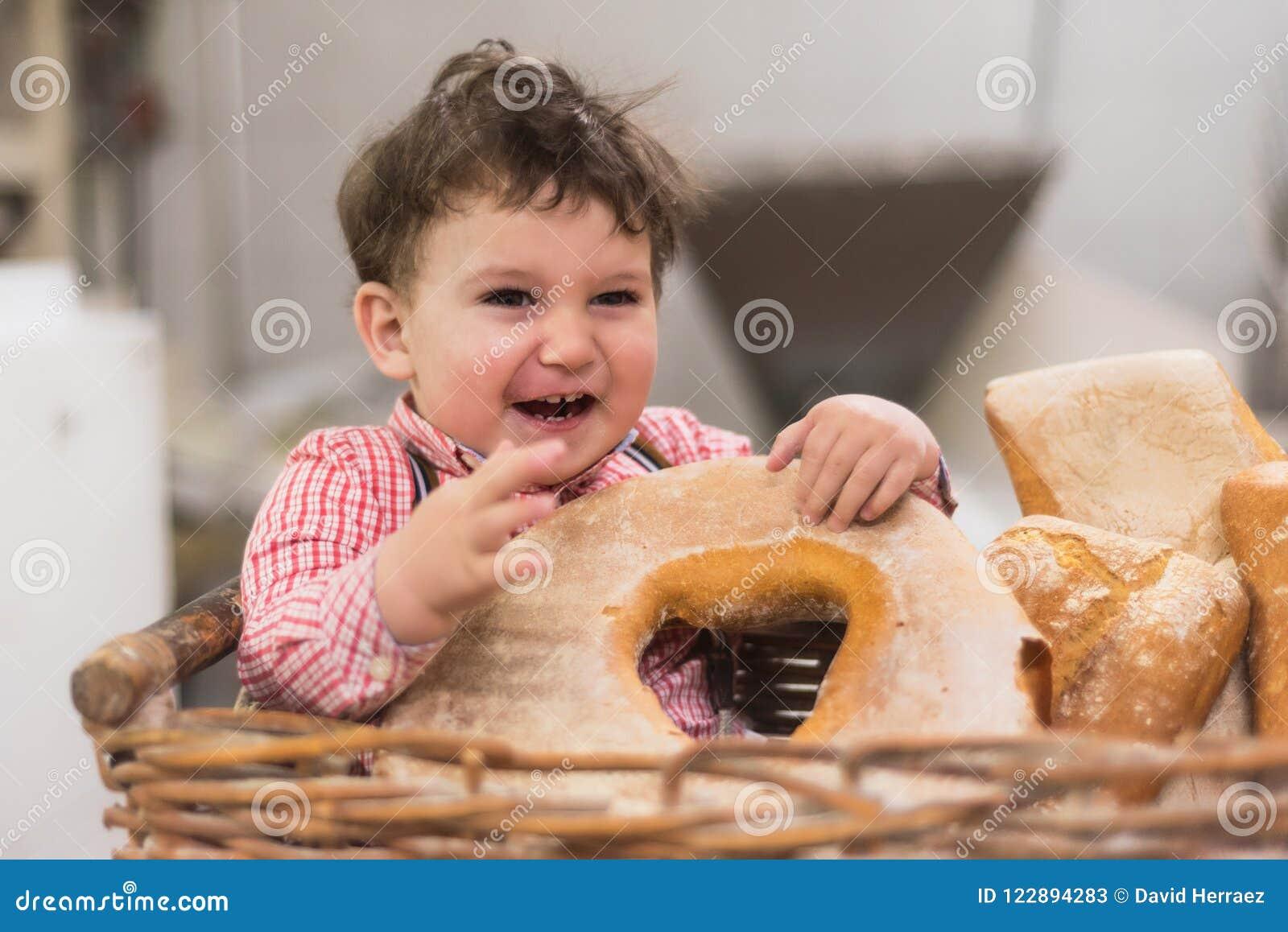 Retrato de um bebê bonito dentro de uma cesta com pão na padaria