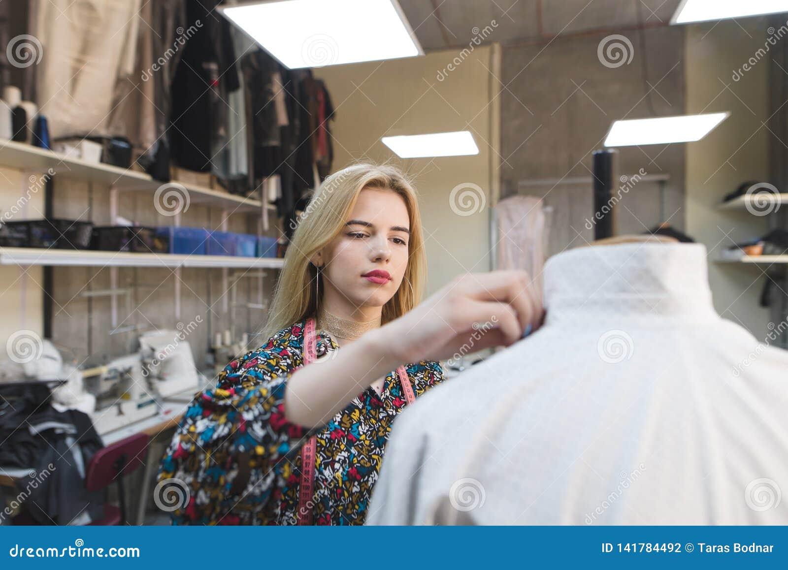 Retrato de um costureiro da menina que crie a roupa em seu próprio estúdio do projeto Desenhador de moda no trabalho