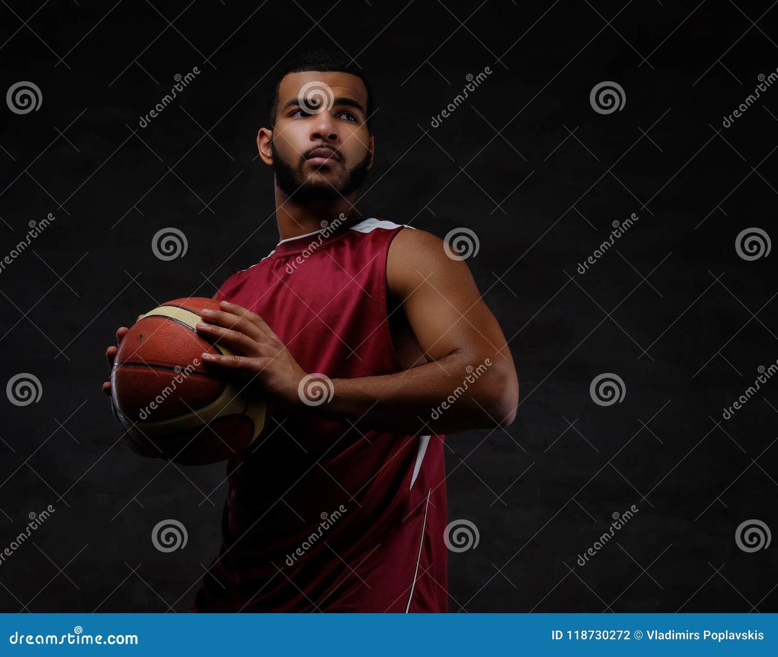 Retrato de um desportista afro-americano Jogador de basquetebol no sportswear com uma bola