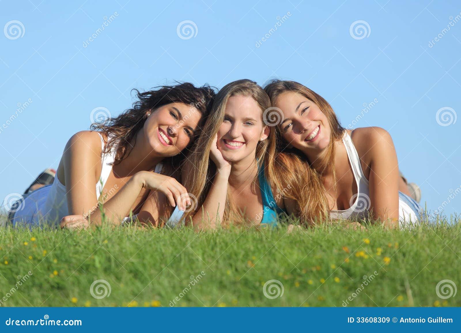 Retrato de um grupo de um encontro de sorriso de três meninas felizes do adolescente na grama