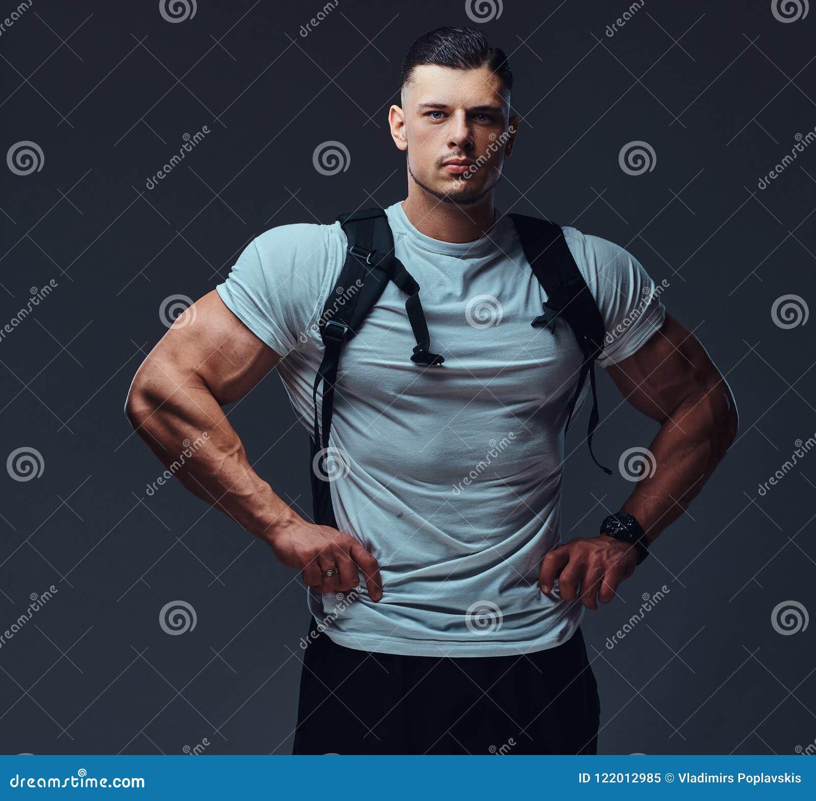 Retrato de um halterofilista considerável muscular no sportswear com a mochila que levanta contra um fundo cinzento