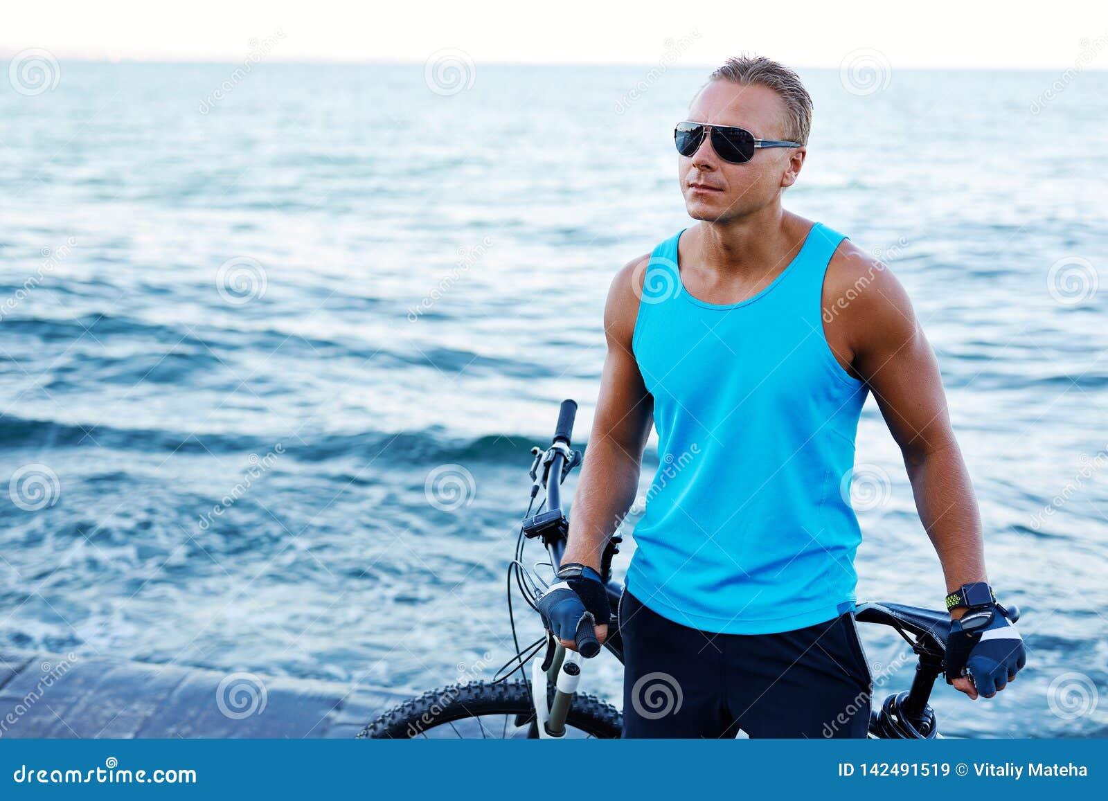 Retrato de um homem atlético louro considerável com bicicleta fora na praia
