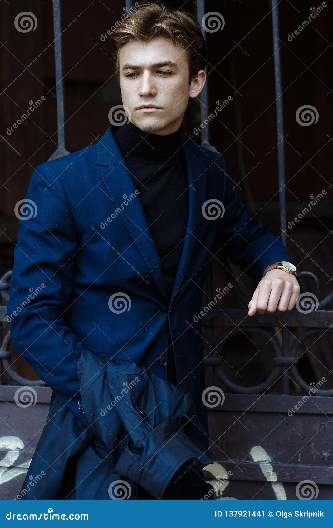 Retrato de um homem atrativo em um terno e em uma camiseta preta, close-up, em sua mão um relógio de ouro, pose da ninhada, olhan