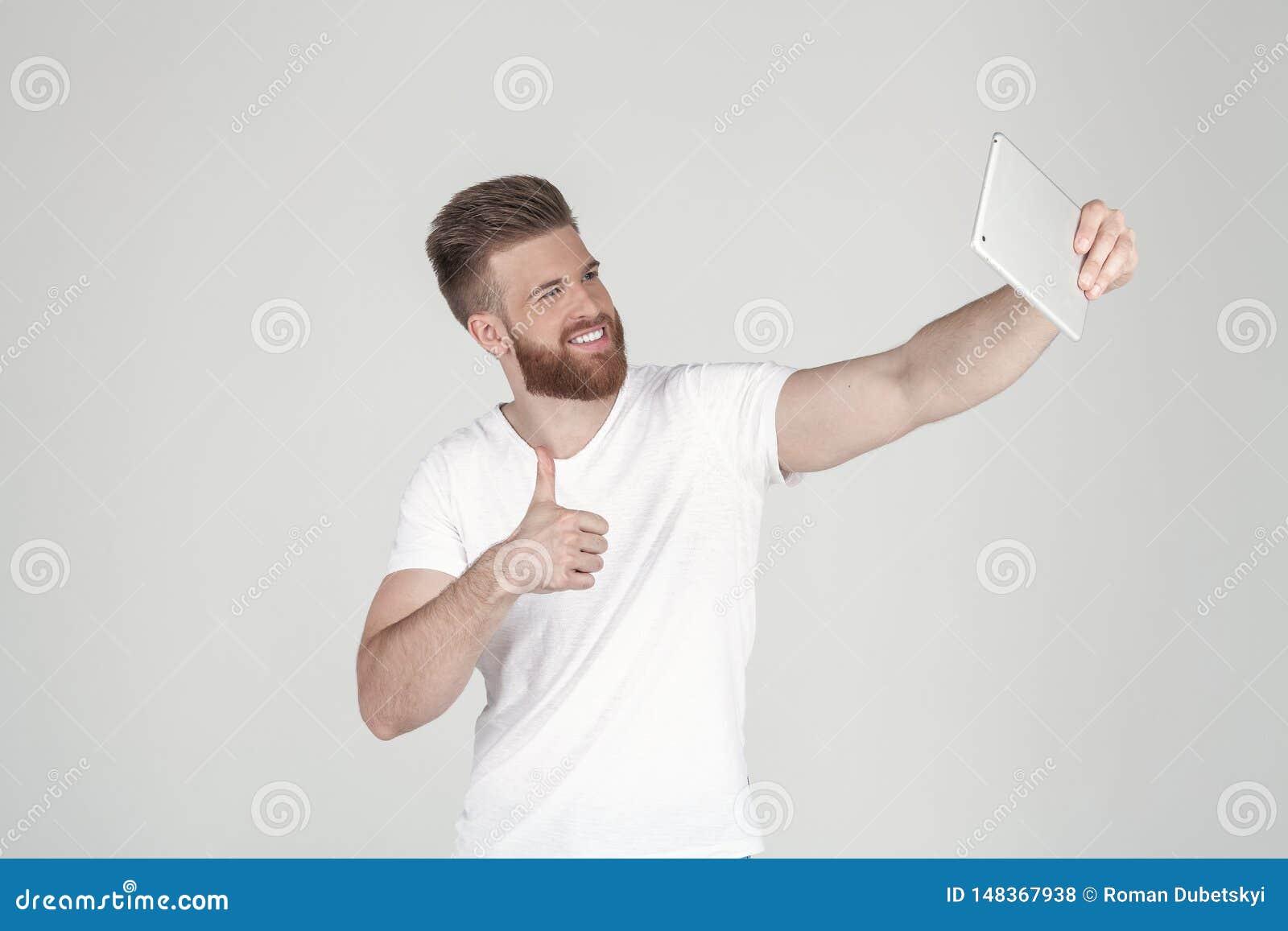 Retrato de um homem bonito com uma barba e um penteado elegante vestidos na roupa ocasional fazendo um sephi em sua tabuleta e