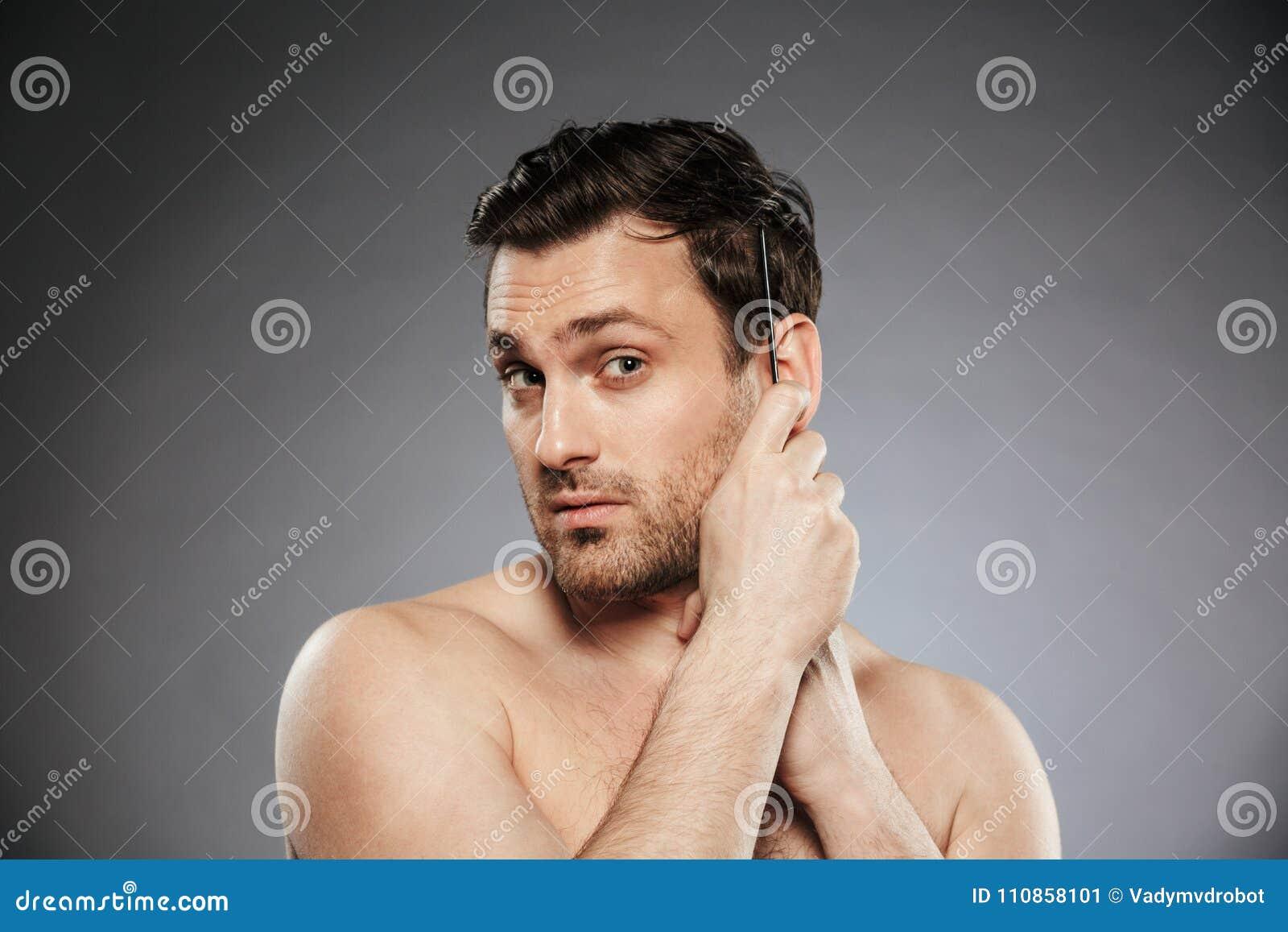 Retrato de um homem descamisado seguro que penteia seu cabelo
