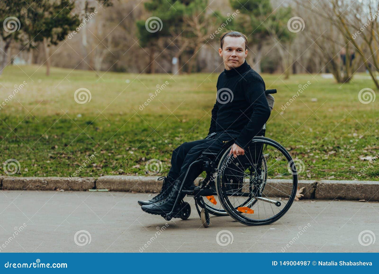 Retrato de um homem feliz em uma cadeira de rodas em um parque