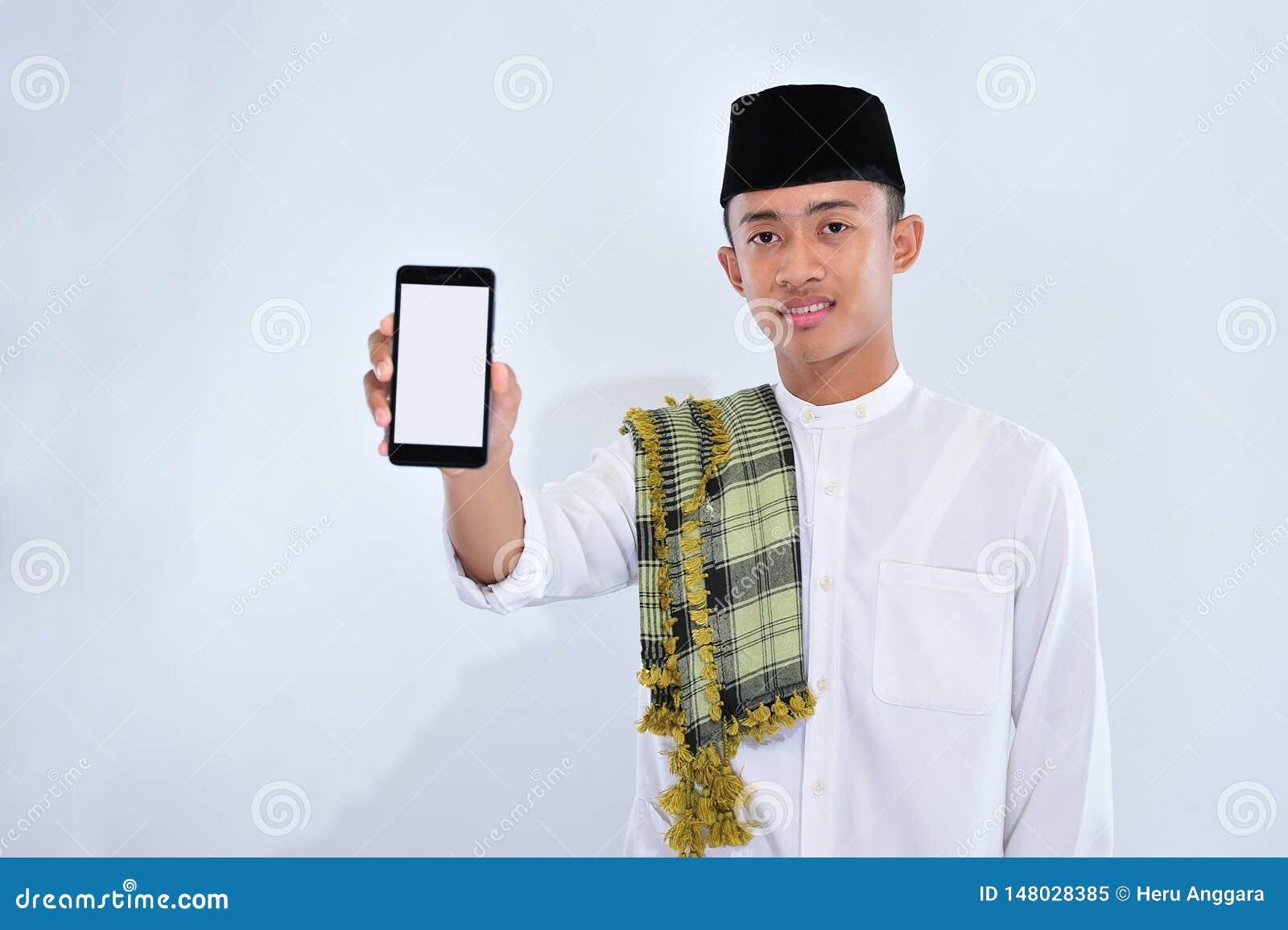Retrato de um homem muçulmano novo de sorriso que aponta no telefone celular branco da tela