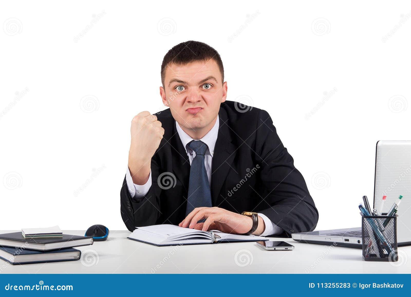 Retrato de um homem de negócios irritado novo que mostra lhe seu punho isolado no fundo branco