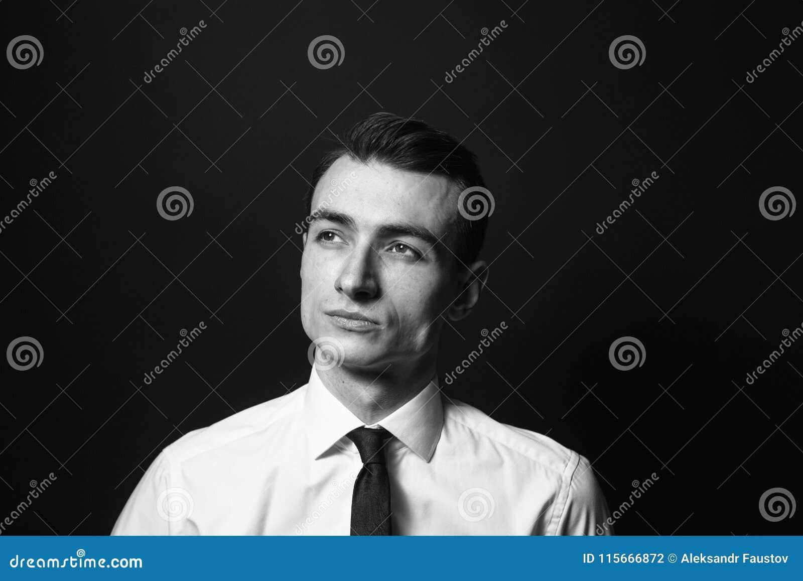 Retrato de um homem novo em uma camisa e em um traje de cerimônia brancos