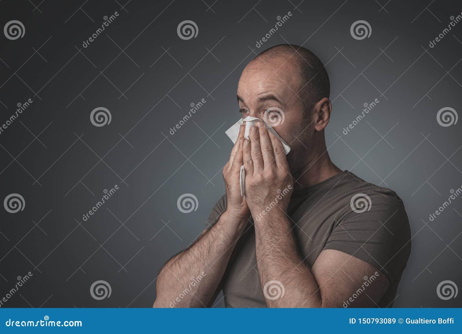 Retrato de um homem que funde seu nariz com um tecido