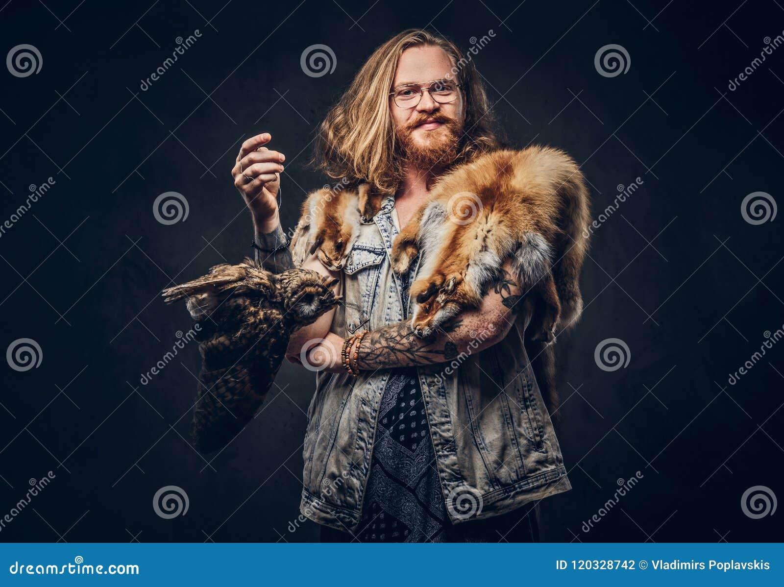 Retrato de um homem tattoed do moderno do ruivo com cabelo exuberante longo e a barba completa vestidos em posses de um t-shirt e