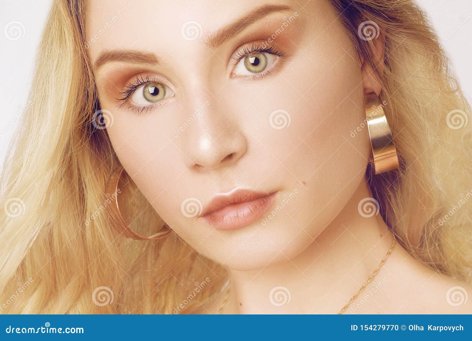 Retrato de um louro bonito com cabelo longo Menina com brincos do ouro, joia A menina com olhos verdes Tiro do est?dio Um jovem