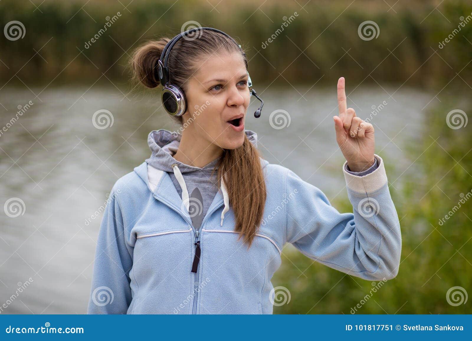 Retrato de um operador de sorriso bonito do serviço ao cliente que veste uns auriculares