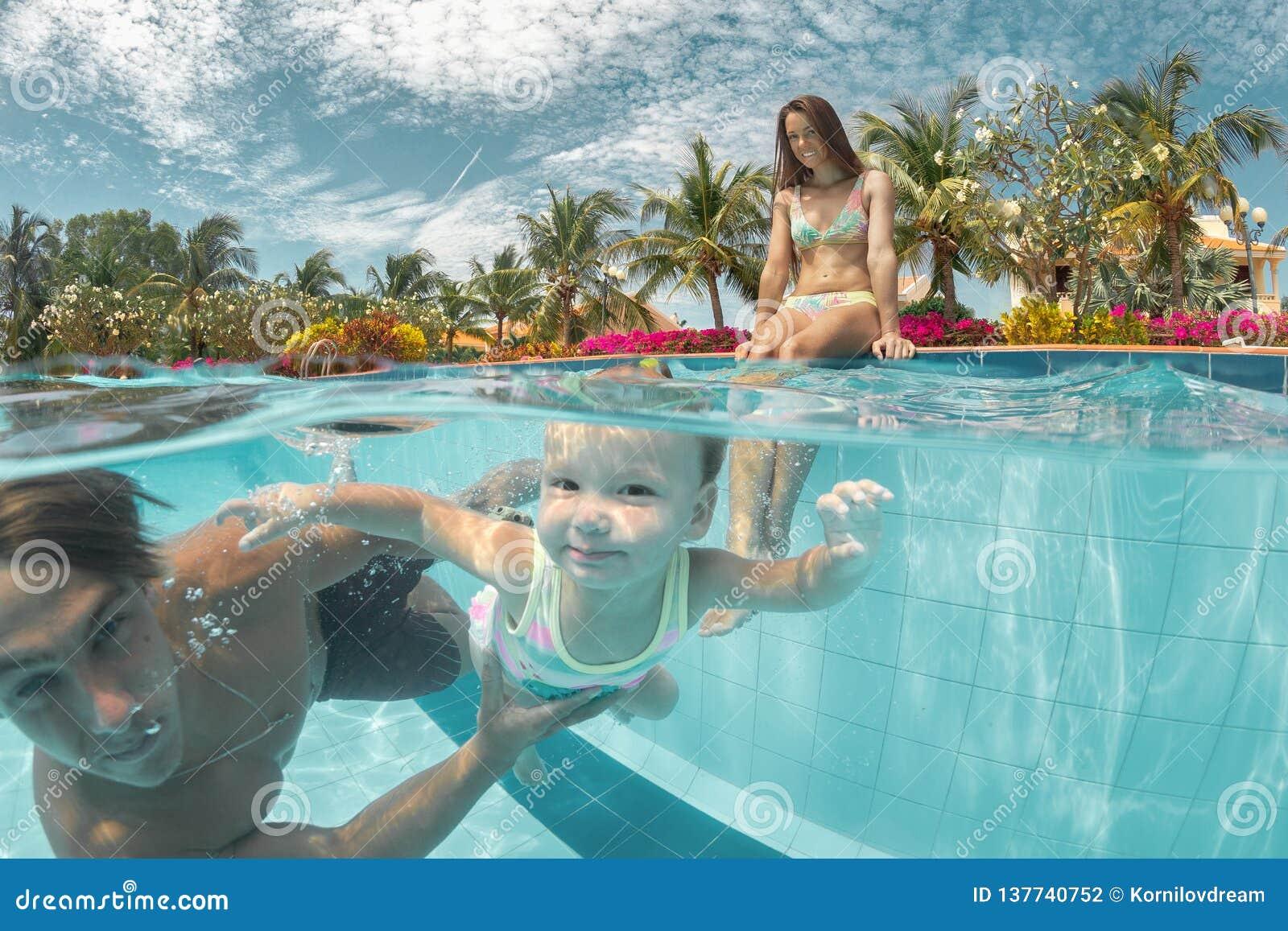 Retrato de um par feliz com a filha na piscina