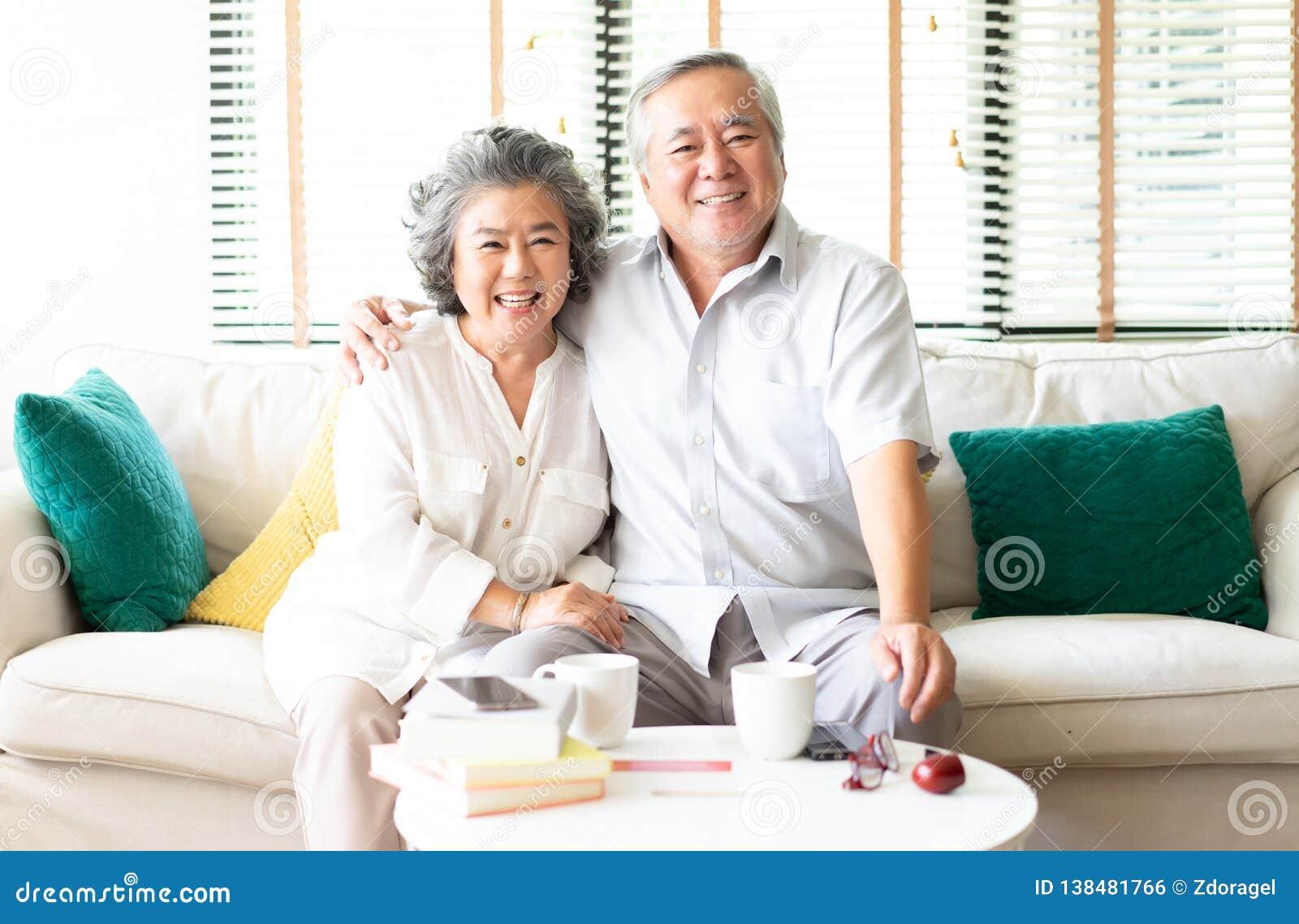 Retrato de um par superior asiático feliz que relaxa em casa no sofá com a esposa que abraça seu marido que sorri na câmera