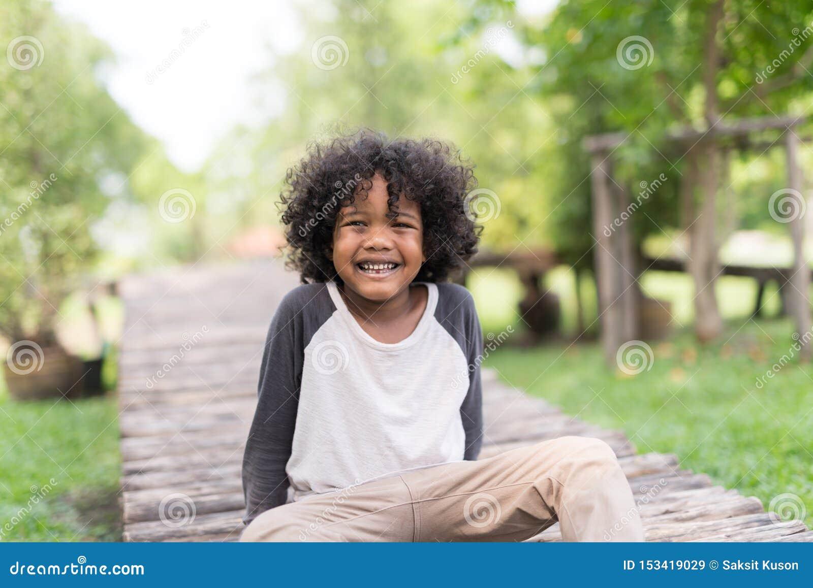Retrato de um rapaz pequeno afro-americano bonito que sorri no parque natural