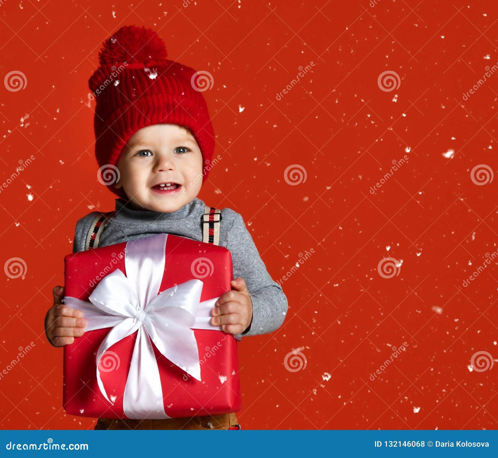 Retrato de um rapaz pequeno em um chapéu vermelho com um pompon guardando uma grande caixa de presente com uma curva branca
