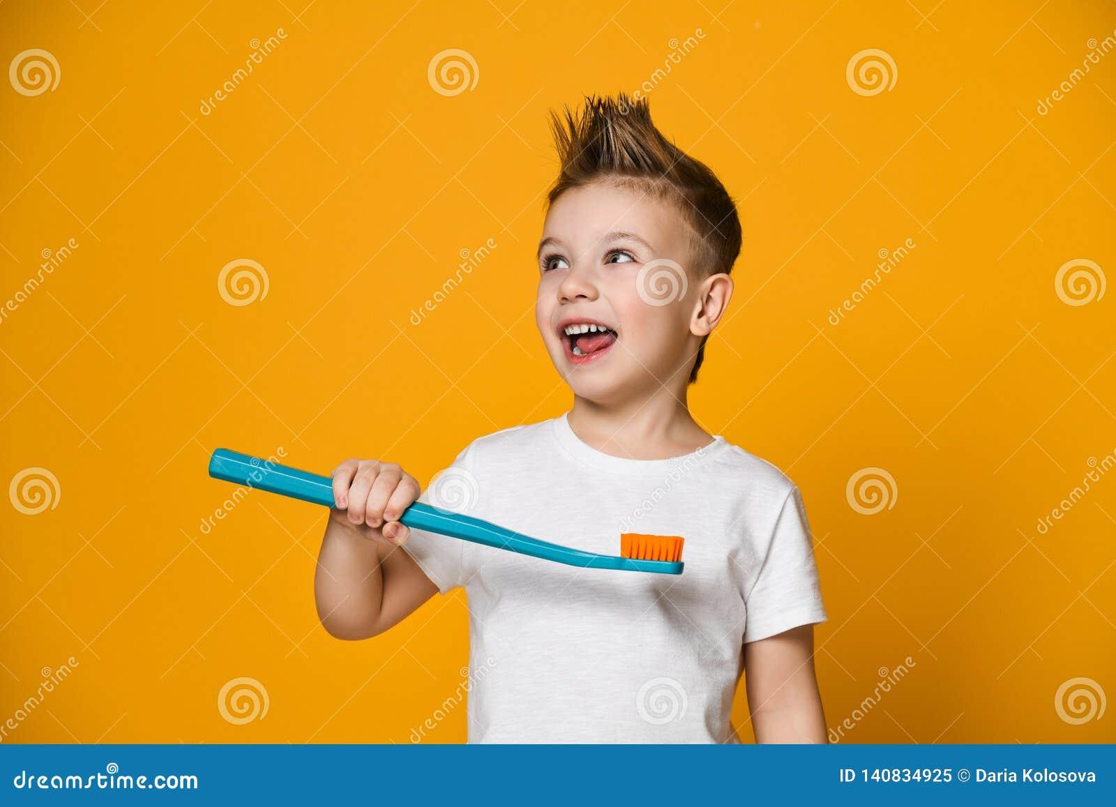 Retrato de um rapaz pequeno que guarda uma escova de dentes sobre o fundo amarelo