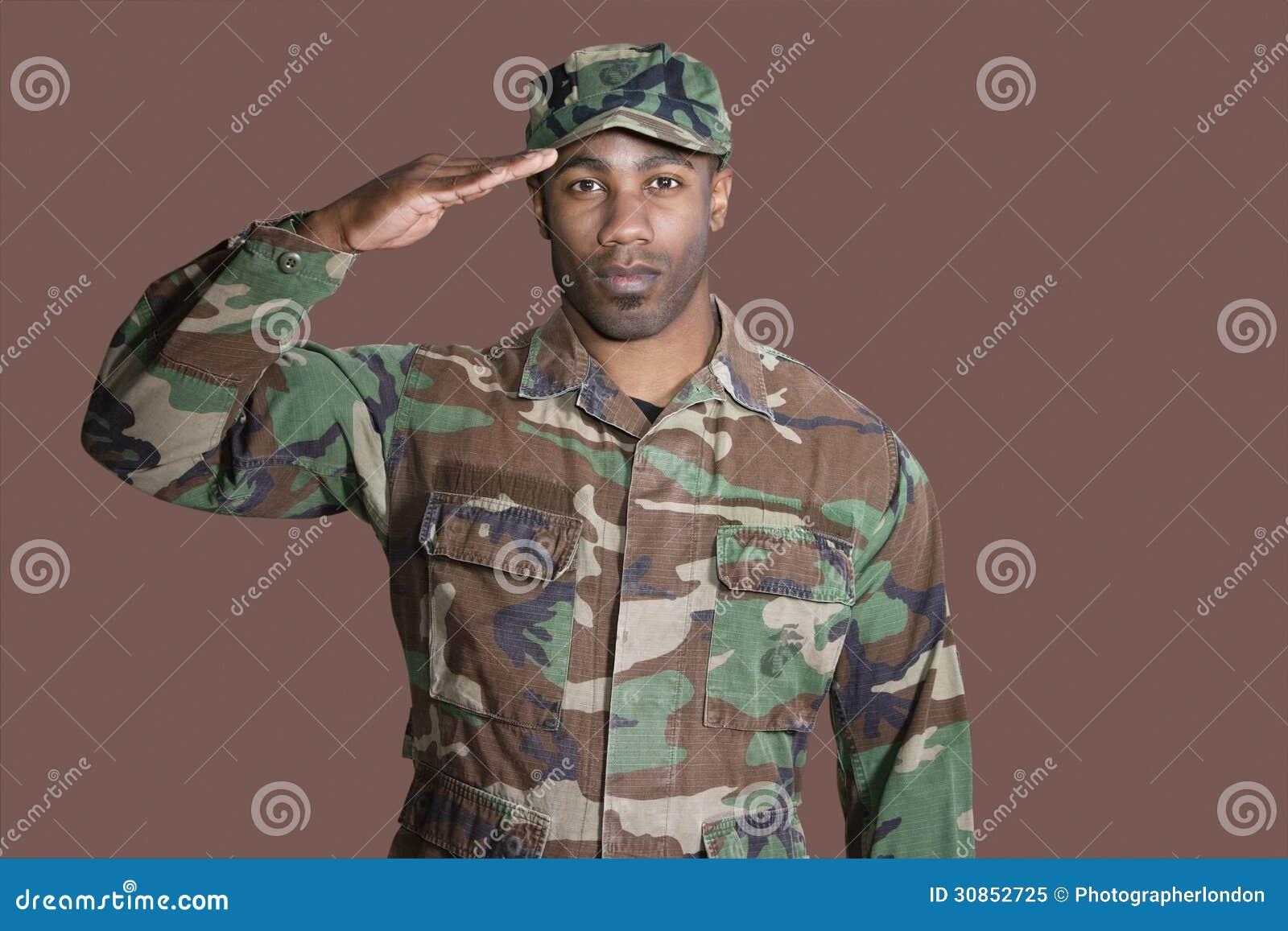 Retrato de um soldado novo dos E.U. Marine Corps do afro-americano que sauda sobre o fundo marrom