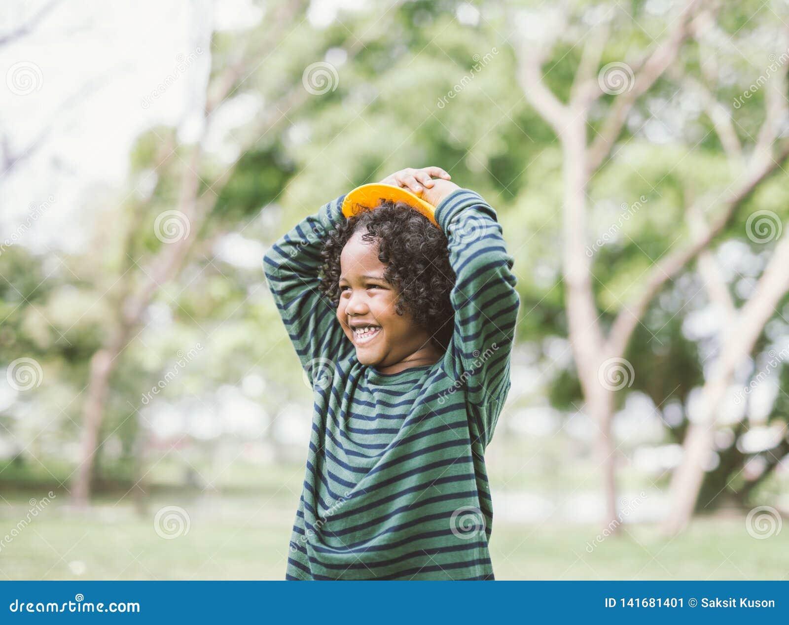 Retrato de um sorriso afro-americano bonito do rapaz pequeno