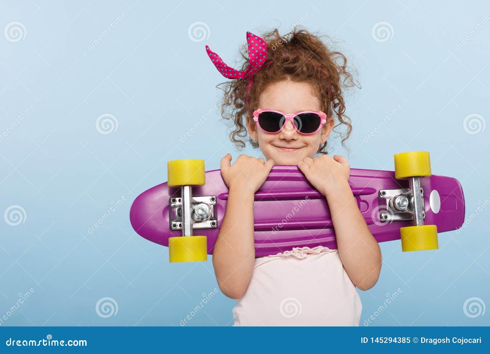 Retrato de uma cara do divertimento de uma menina em ?culos de sol cor-de-rosa, guardando o patim nas m?os, isoladas em um fundo