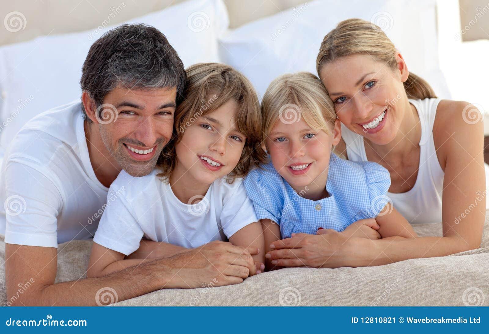 Retrato de uma família alegre que encontra-se em uma cama