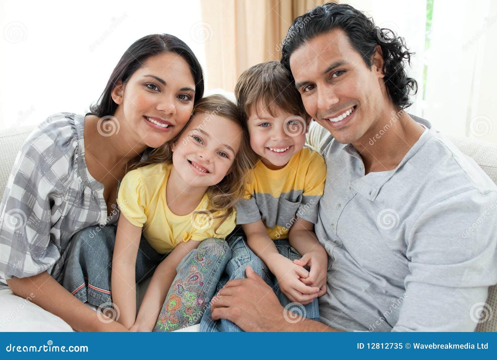 Retrato de uma família de sorriso que senta-se no sofá