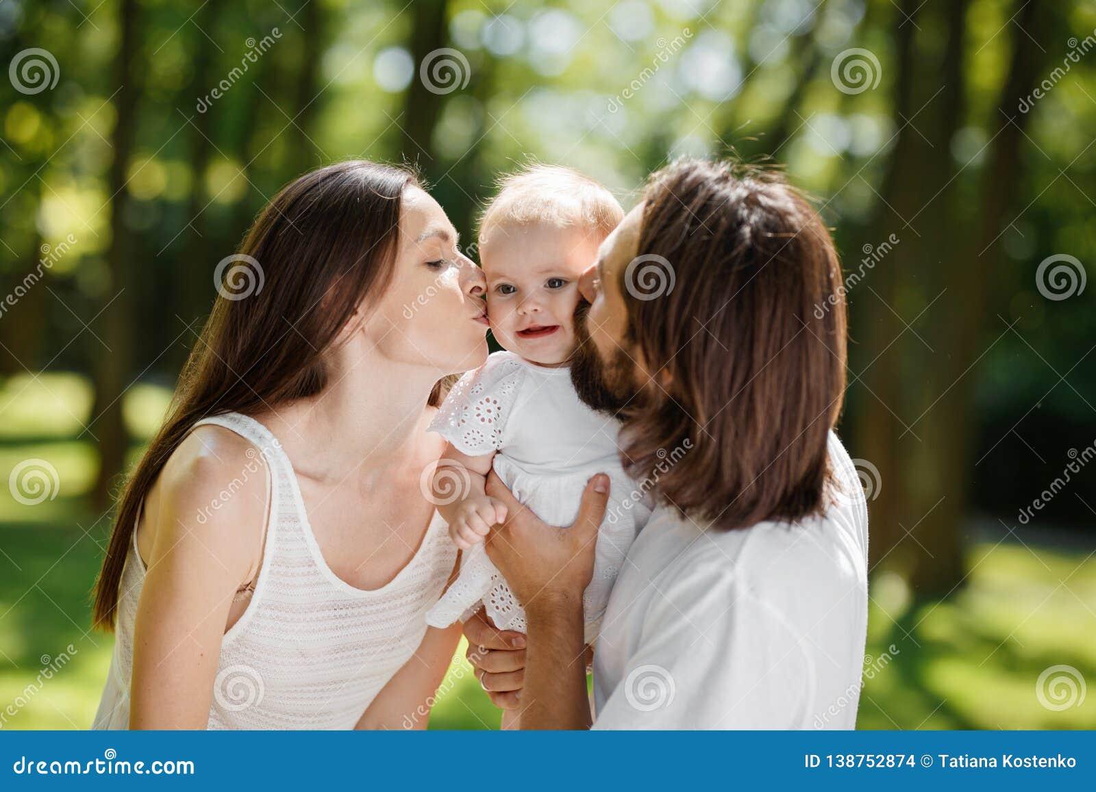 Retrato de uma família feliz Pai de cabelo escuro novo e sua esposa bonita para beijar sua filha adorável do bebê