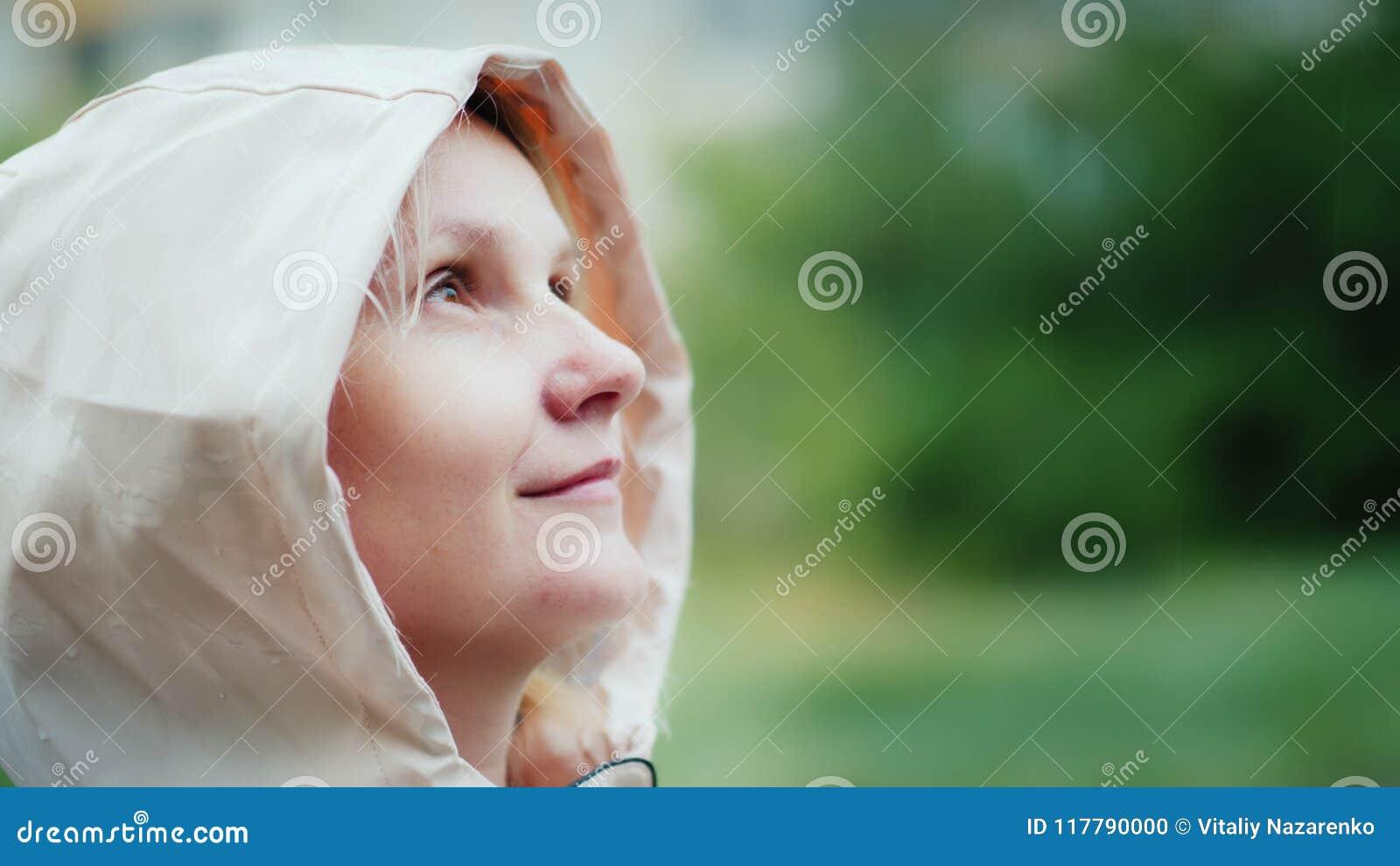 Retrato de uma jovem mulher, apreciando a chuva de mola, olhando acima Caminhada e aventura, conceito do frescor