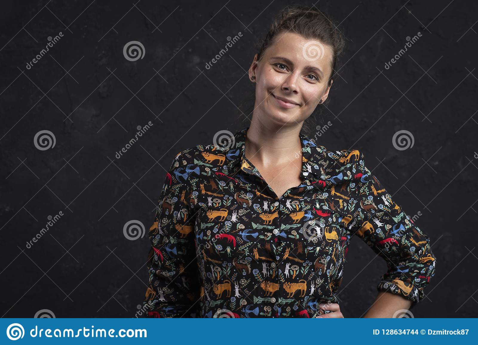 Retrato de uma jovem mulher em um fundo preto Menina natural atrativa em uma camisa preta Menina do tiro do estúdio que olha a câ