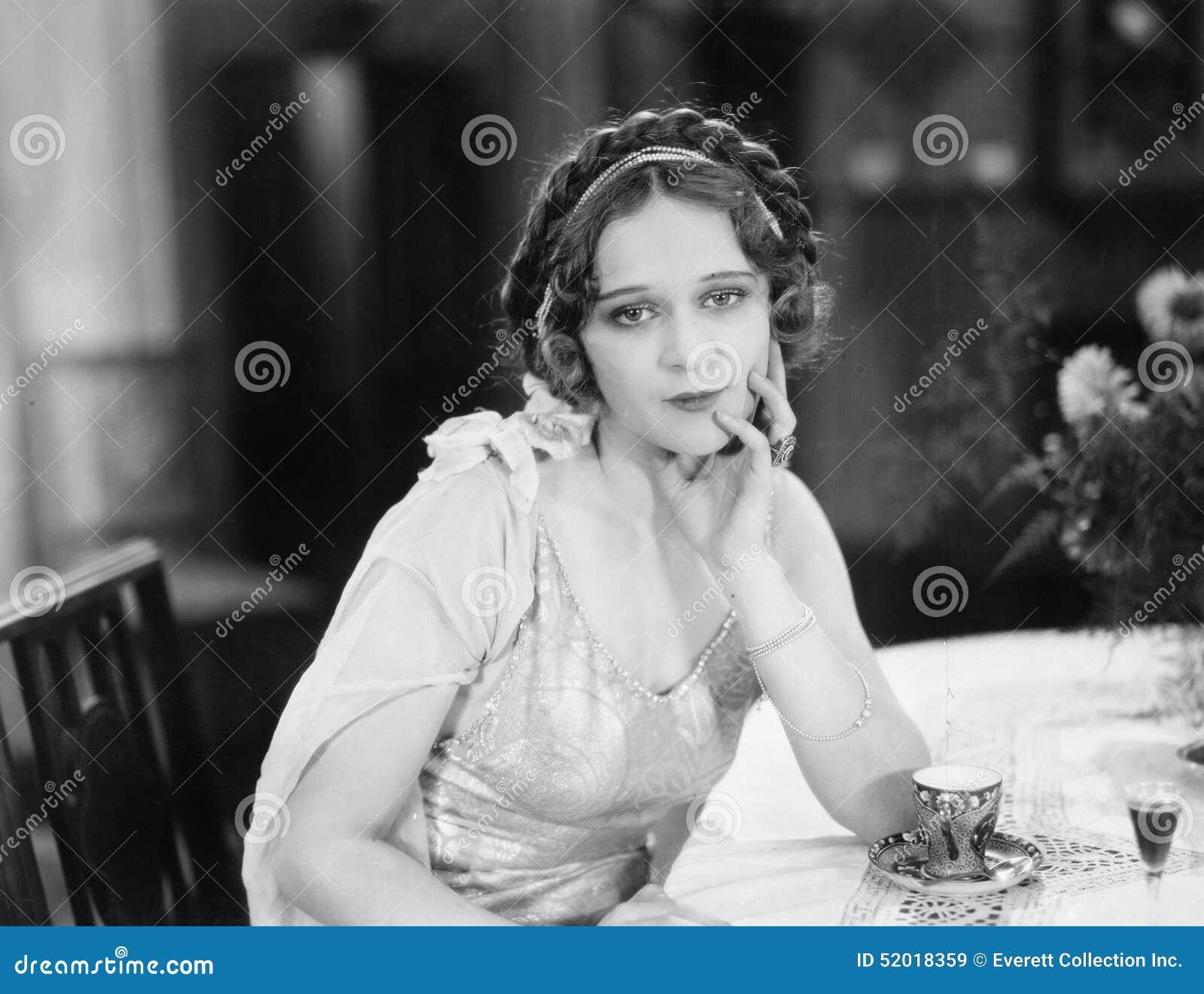 Retrato de uma jovem mulher que senta-se em uma tabela e que pensa em um restaurante (todas as pessoas descritas não são umas viv