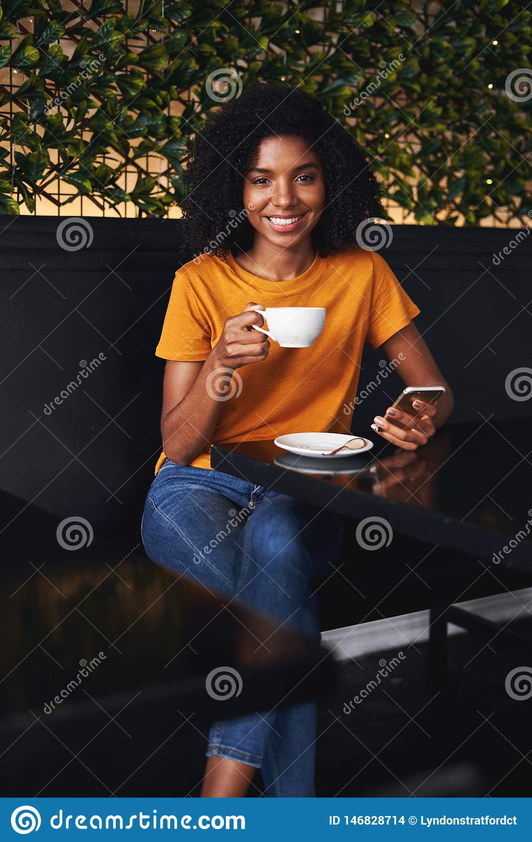 Retrato de uma jovem mulher que senta-se no café com smartphone